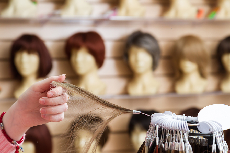 Woman's hand holding wig accessories with wigs on wig stands in the background.